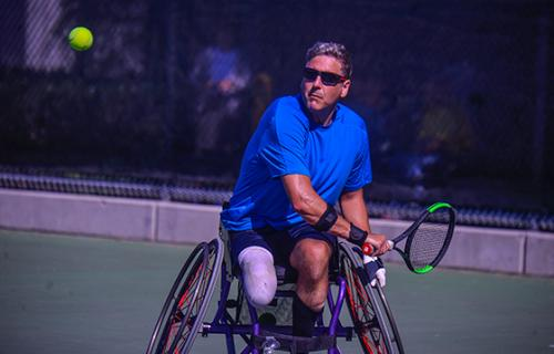 An older single leg male amputee in a bright blue shirt and black shorts prepares to hit a tennis ball that is several feet in front of his face. The athlete is seated in a tennis wheelchair and is on an outdoor tennis court during a sunny summer day.