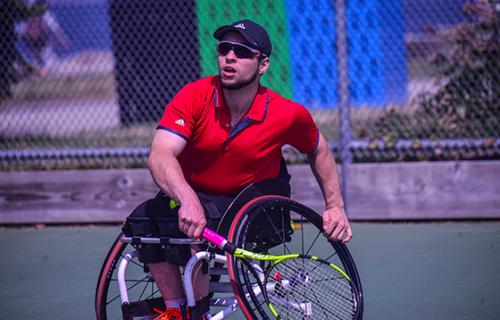 A Wheelchair Tennis player in a red shirt, black shorts, black hat and sunglasses competes.  His left hand hold his wheel and right hand holds a racket.