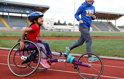 a young asian girl in a red shirt and purple racing chair rolls along an outdoor track with a big smile as a white woman in a blue sweatshirt and gray track pants runs besides her with a smile